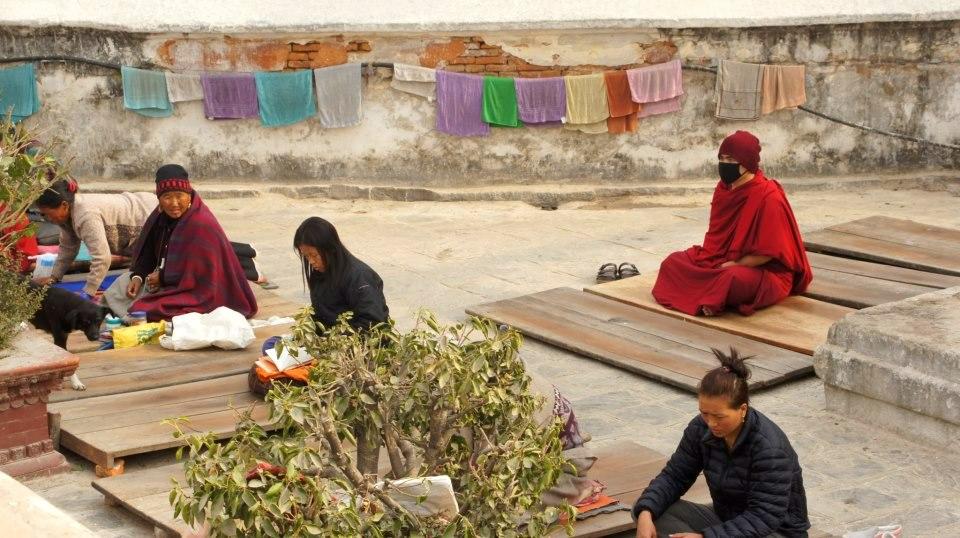 Moine et pélerins en prière Bodnath Kathmandou Népal