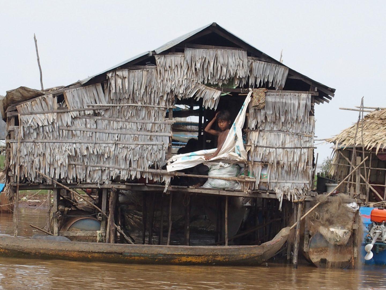 Enfant et maison sur pilotis Tonle Sap Cambodge