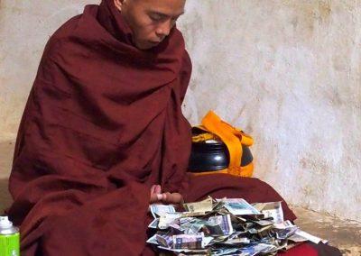 Aumones sur genoux moine Bagan Birmanie