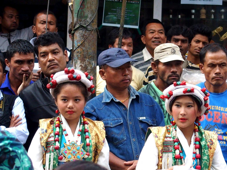 Jeunes filles en habit traditionnel et hommes au visage patibulaire