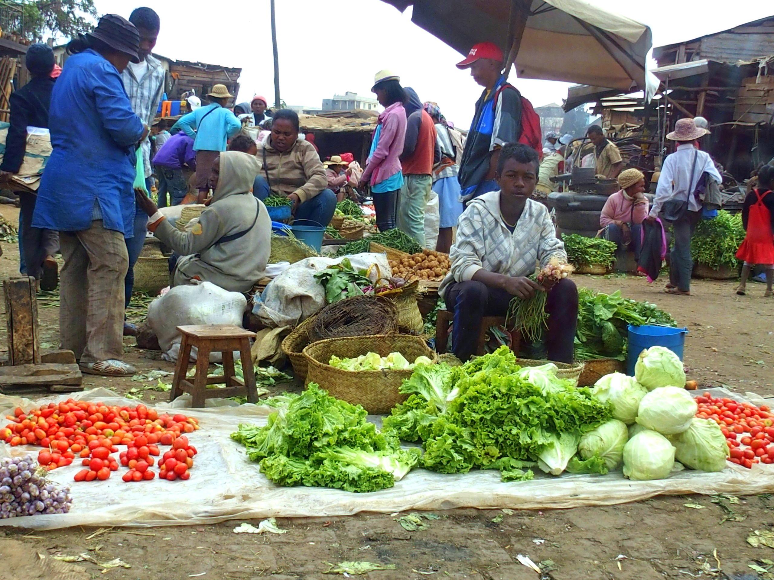 Jeunes vendeur fruits et légumes sur marché Madagascar.