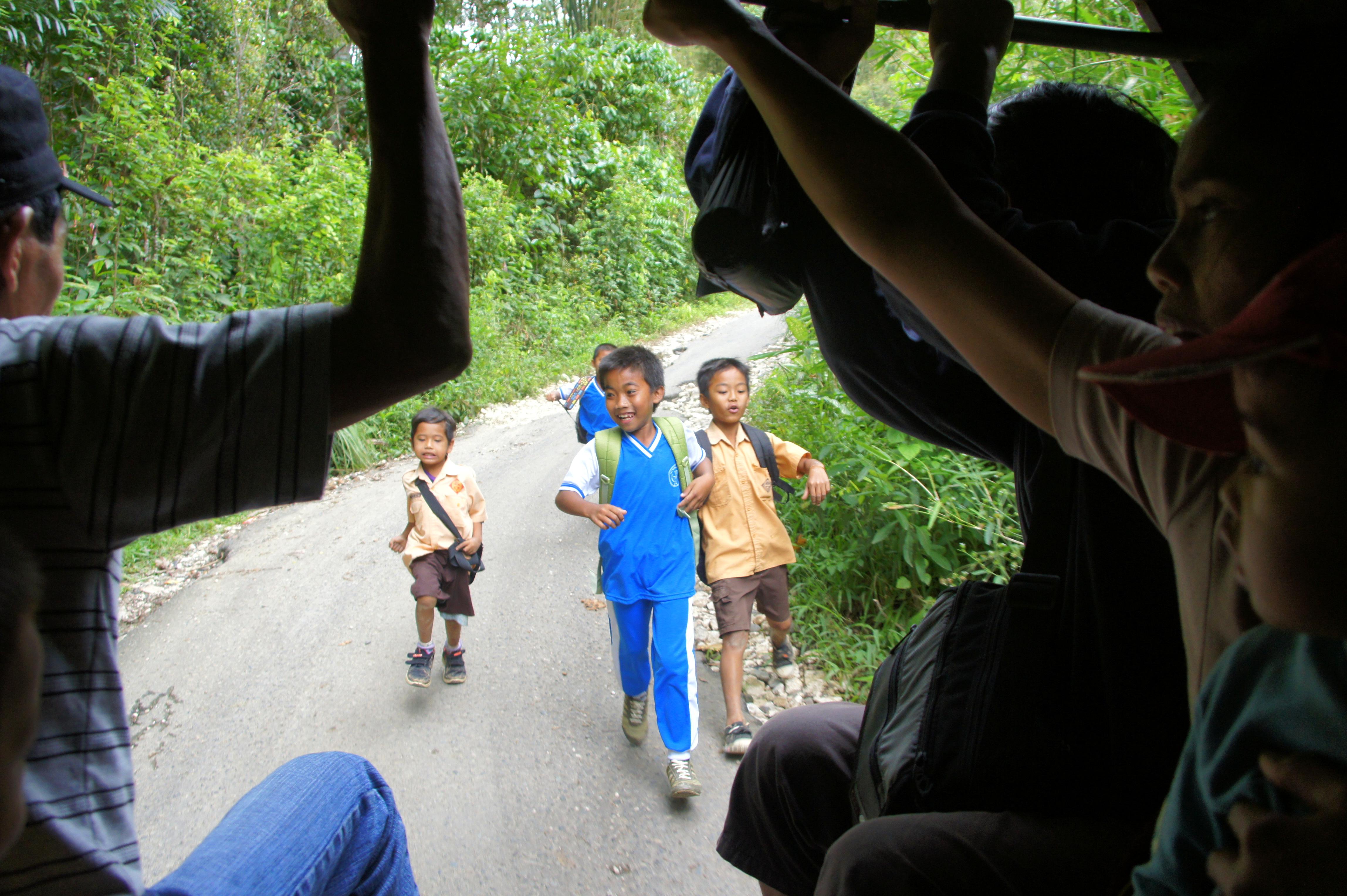 Enfants qui courrent derrière le bémo Sulawesi