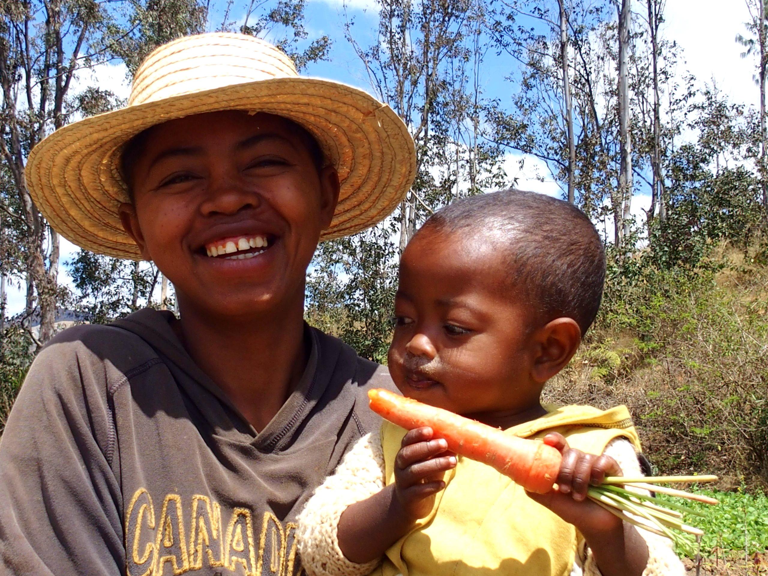Mère et fils mangeur de carotte dans un champ à Madagascar