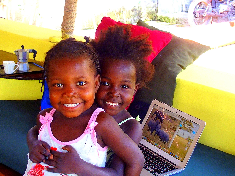 Sourire de deux fillettes Ibo qui découvrent des photos d'éléphants sur mon ordinateur - Mozambique