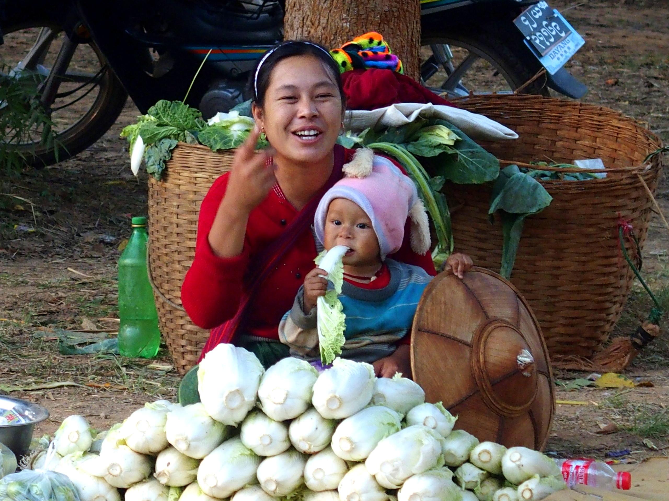 Vendeuse et enfant mangeur de choux marché Bago Myanmar