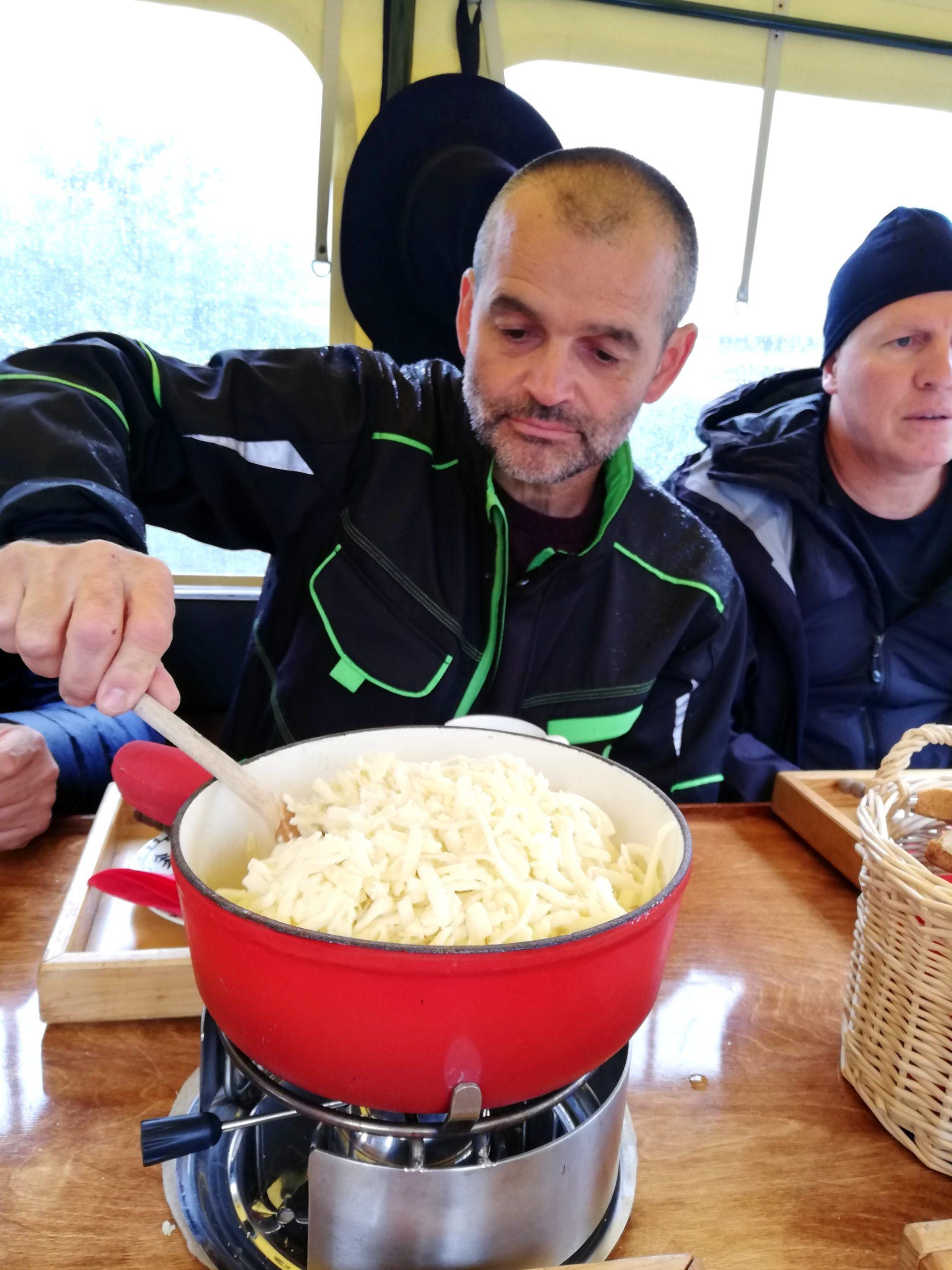 Mélange du fromage à raclette dans char à fondue Suisse